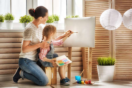 draw: Happy family. Mother and daughter together paint. Adult woman helps the child girl.