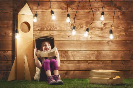 toy box: Child girl in an astronaut costume with toy rocket playing and dreaming of becoming a spacemen. Stock Photo