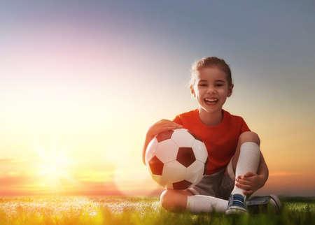 jugador de futbol: Niño lindo sueños de convertirse en un jugador de fútbol. La muchacha juega al fútbol. Foto de archivo
