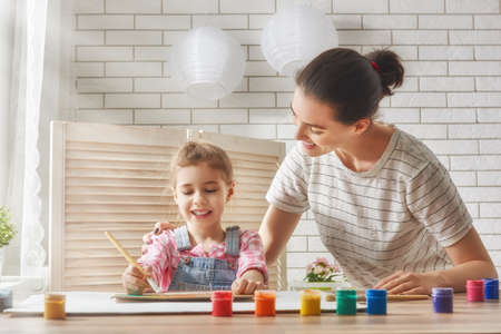 daughter: Happy family. Mother and daughter together paint. Adult woman helps the child girl.