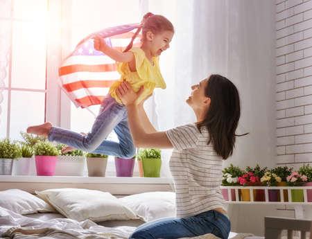 Patriottische vakantie. Gelukkige familie, moeder en haar dochter kind meisje met Amerikaanse vlag thuis. VS vieren 4 juli.