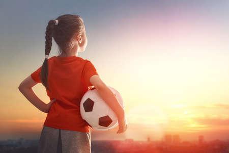 Leuk weinig kind droomt ervan om een ??voetballer. Het meisje speelt voetbal. Stockfoto - 58218117
