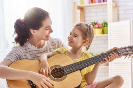 teaching: Happy family. Mother and daughter playing guitar together. Adult woman playing guitar for child girl.