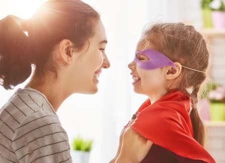 Gelukkige familie bereidt zich voor op een kostuum partij. Moeder en haar kind meisje samen spelen. Meisje in Superman kostuum.