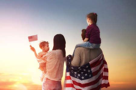 julio: fiesta patriótica. Feliz familia, padres e hijas muchachas de los niños con la bandera americana al aire libre. EE.UU. celebrar el 4 de julio.