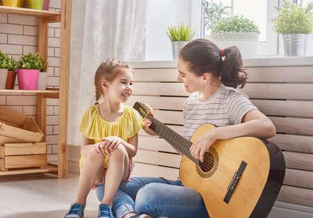 niños sentados: Familia feliz. Madre e hija a tocar la guitarra juntos. mujer adulta tocar la guitarra para niñas. Foto de archivo