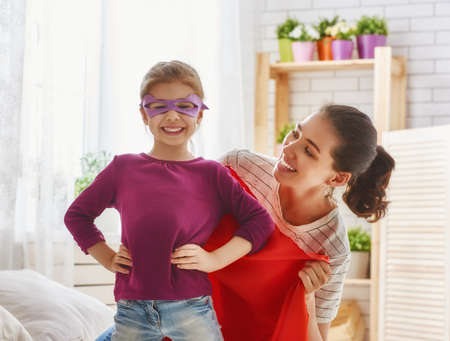 primp: Happy family is preparing for a costume party. Mother and her child girl playing together. Girl in Supermans costume.