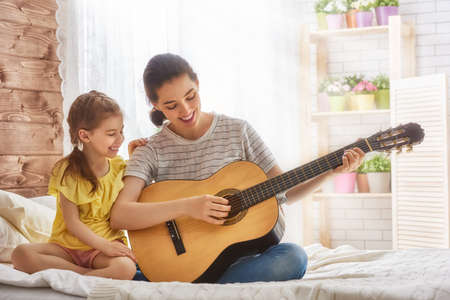 art lessons: Happy family. Mother and daughter playing guitar together. Adult woman playing guitar for child girl.