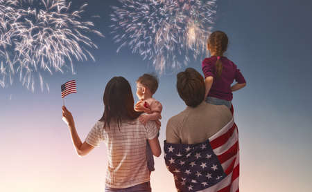 Patriotic holiday. Happy family, parents and daughters children girls with American flag outdoors. USA celebrate 4th of July.