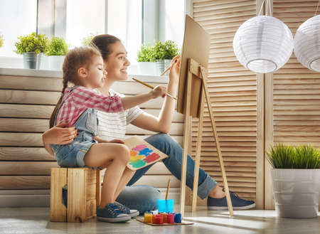 helps: Happy family. Mother and daughter together paint. Adult woman helps the child girl.