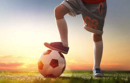 uniform green shoe: Cute little child dreams of becoming a soccer player. Child plays football.
