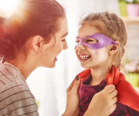 Happy family is preparing for a costume party. Mother and her child girl playing together. Girl in Supermans costume.