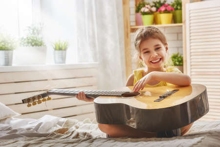 girl playing guitar: Cute little child girl playing guitar.