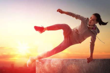 joven mujer deportiva al aire libre. la chica se dedica en el parkour. Foto de archivo