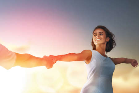 inlove: Happy couple in love. Stunning sensual portrait of young stylish fashion couple outdoors. Young woman holds the hand of her boyfriend on background sunset sky. Stock Photo