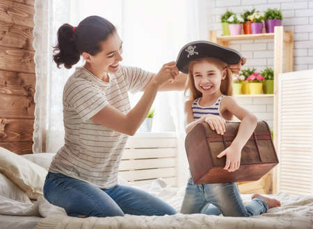 primp: Happy family is preparing for a costume party. Mother and her child girl playing together. Girl in pirates costume. Stock Photo