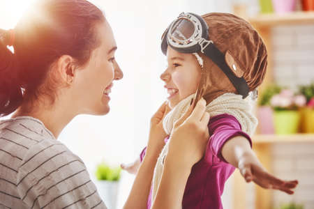 primp: Happy family is preparing for a costume party. Mother and her child girl playing together. Girl in pilots costume.