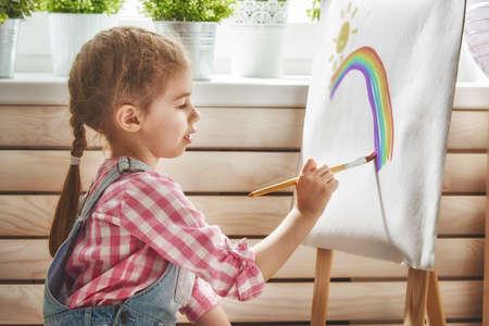 Glückliches kleines Kind zeichnet Lacke. Süßes Mädchen engagiert in Kreativität.