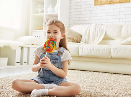 funny child girl plays at home. girl eating candy and resting. recreation and entertainment at home.