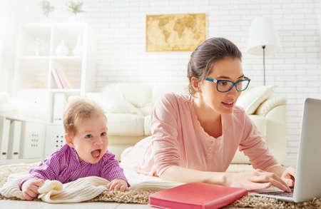 madre trabajando: familia feliz. madre y el bebé. una madre joven que trabaja con el ordenador portátil en casa