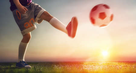 football play: Cute little child dreams of becoming a soccer player. Child plays football.