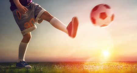 patada: Niño lindo sueños de convertirse en un jugador de fútbol. Niño juega al fútbol.