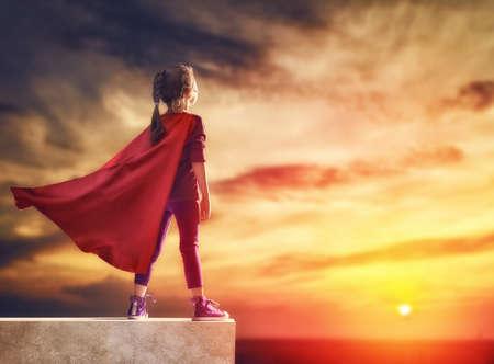 Kleines Kind spielt Superheld. Kind auf dem Hintergrund des Sonnenuntergangs Himmel. Mädchen Power-Konzept Standard-Bild