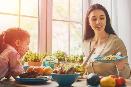 Cena de familia feliz juntos sentados en la mesa de madera rústica. La madre y su hija disfrutando de la cena de la familia juntos. Foto de archivo
