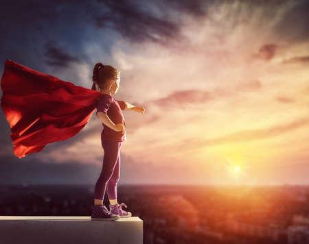 작은 아이는 슈퍼 히어로을한다. 일몰 하늘의 배경에 아이. 여자 전원 개념