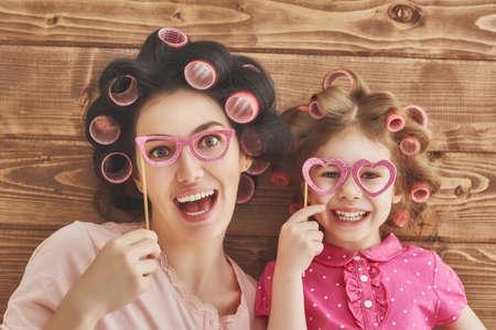 Família engraçada! Matriz e sua menina criança filha com acessórios de papel.