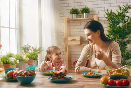 Gelukkige familie eten samen zitten aan de rustieke houten tafel. Moeder en haar dochter die familie diner samen. Stockfoto - 59181572