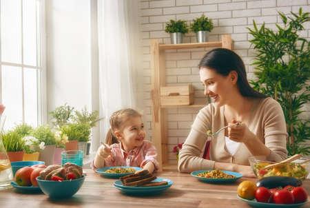 Glückliche Familie zusammen mit Abendessen sitzt am rustikalen Holztisch. Mutter und ihre Tochter gemeinsam genießen Familie Abendessen.
