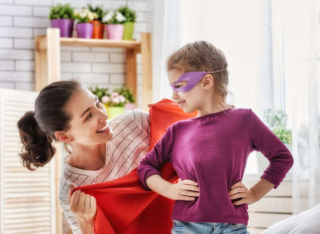 child smile: Happy family is preparing for a costume party. Mother and her child girl playing together. Girl in heroes costume.