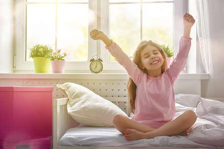 despertarse: Una buena chica niño disfruta mañana de sol. Buenos días en casa. La muchacha del niño se despierta de su sueño. Foto de archivo