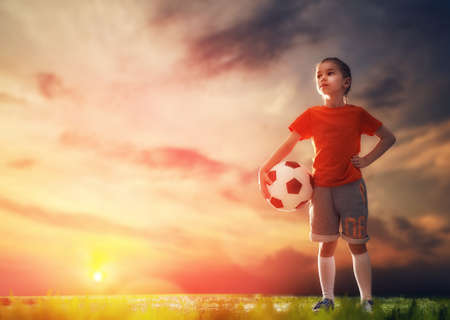 Leuk weinig kind droomt ervan om een ??voetballer. Kind speelt voetbal. Stockfoto - 59181627