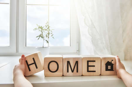 Gelukkig meisje spelen met blokken en plezier maken. Blokken hebben letters. Het kind zet het woord Home. Stockfoto - 61033963