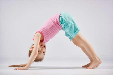 Cute little child girl enjoying yoga.