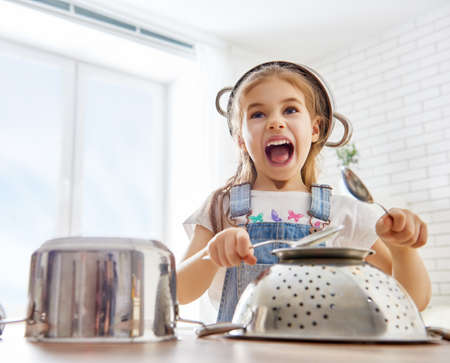 playing with spoon: cute little child girl playing with utensils. Stock Photo
