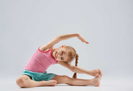 Cute little child girl enjoying yoga.
