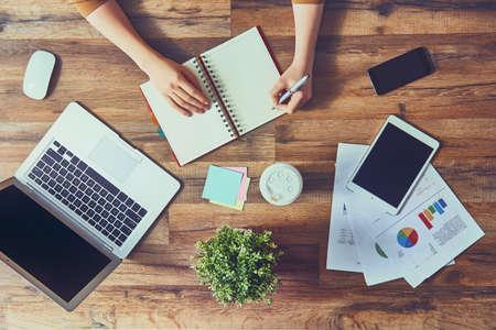 Frau, die Notizen in einem Notizbuch sitzt an ihrem Arbeitsplatz im Büro. Draufsicht Nahaufnahmen. Standard-Bild - 61034023