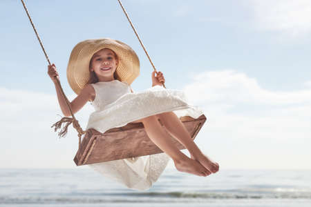 Gelukkig lachend kind meisje op de schommel in de zomer dag