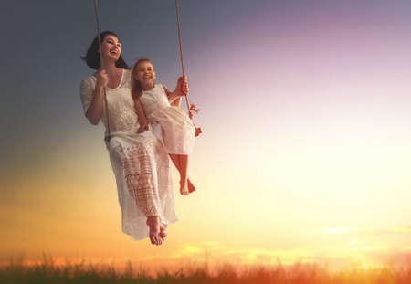 幸せな愛する家族!若い母親と彼女の子娘ブランコの揺れと夏を笑いながら夜の屋外。