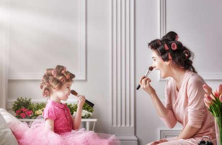 mama e hija: amante de la familia feliz. La madre y la hija están haciendo el pelo y divertirse. Madre y el niño que hace su maquillaje sentado en la cama en el dormitorio.