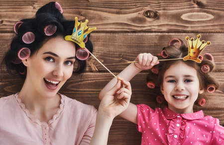 Familia divertida! La madre y su hija niña niño con un accesorios de papel. niño divertido belleza y mamá sosteniendo la corona de papel en el palillo.