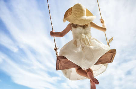 Happy child girl on swing in summer day