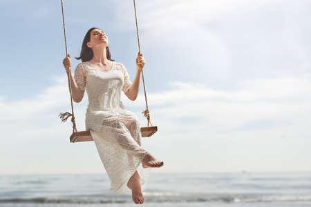 jolie jeune fille: belle jeune femme sur une balançoire le jour de l'été en plein air