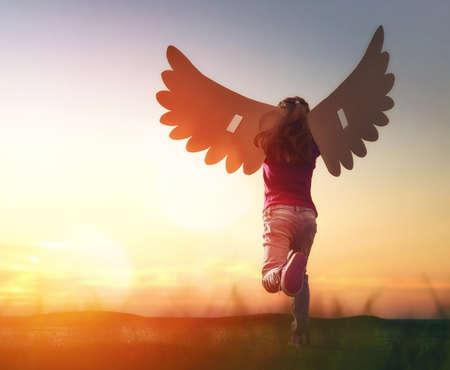 Jogos da menina ao ar livre. Criança no fundo do céu do por do sol. Kid com as asas de um pássaro sonhos de vôo. Imagens