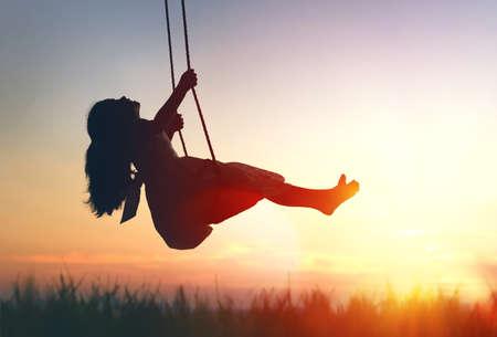 Menina da criança de riso feliz no balanço no por do sol do verão