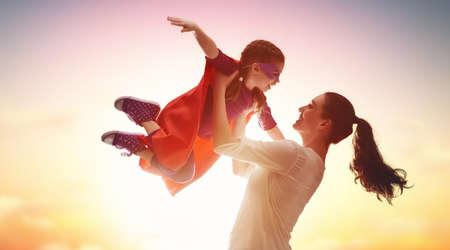 La madre y su niña niño jugando juntos. Niño en el traje de un superhéroe.
