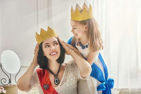 Glückliche liebevolle Familie für ein Kostümfest vorbereitet. Mutter und ihr Kind zu spielen Mädchen zusammen. Schöne Königin und Prinzessin in Goldkronen. Standard-Bild - 61415134